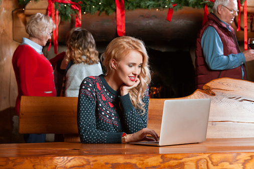 Woman Using Computer During Christmas Stock Photo - Download Image Now