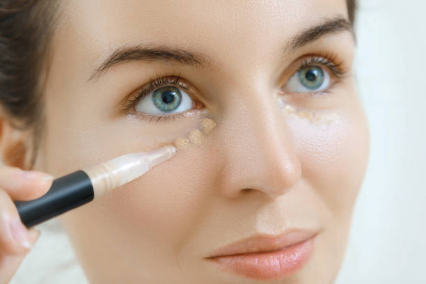 Woman using concealer Woman using concealer for under eye circles nude women pics stock pictures, royalty-free photos & images