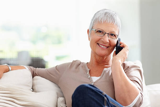 Woman using cordless phone Closeup of beautiful mature woman talking on telephone cordless phone stock pictures, royalty-free photos & images