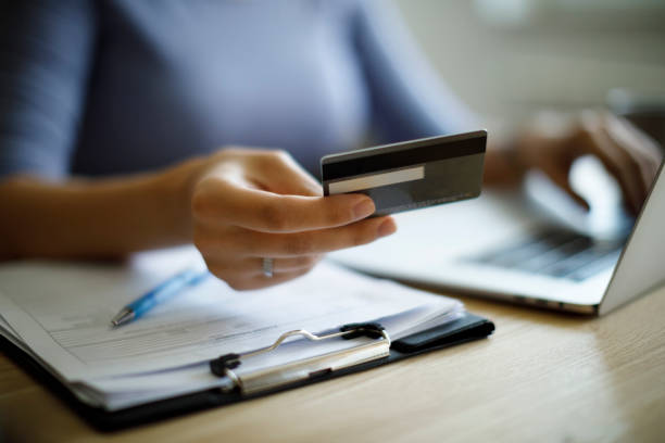Woman using credit card and laptop to pay bills stock photo