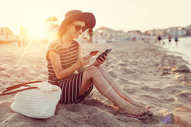 Woman using credit card at the beach stock photo