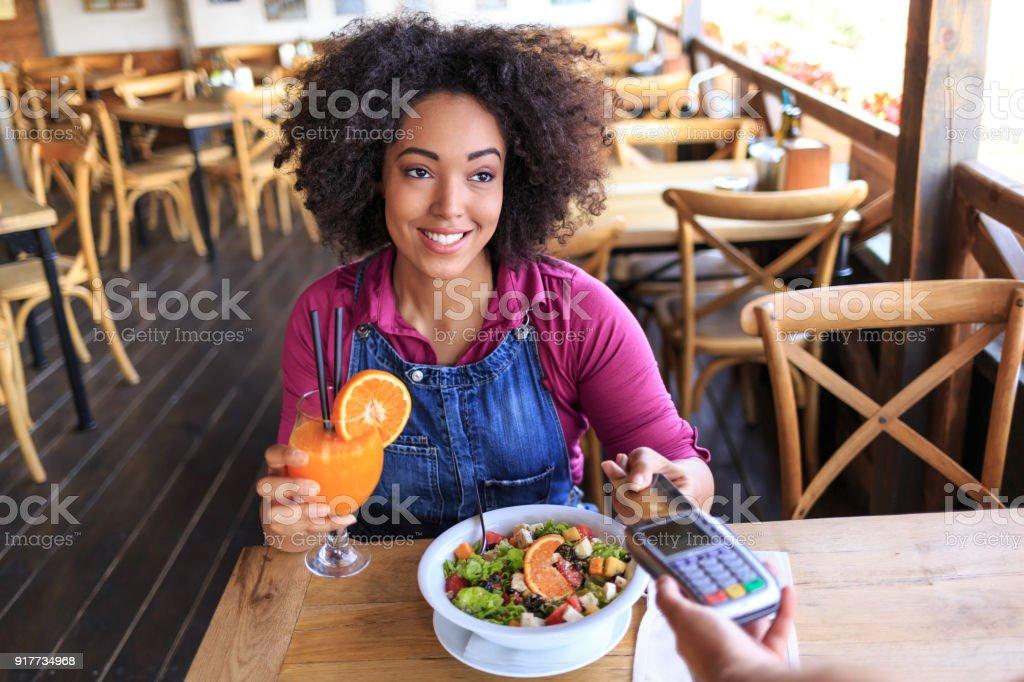 Frau mit Kreditkarte für kontaktloses Bezahlen im restaurant – Foto