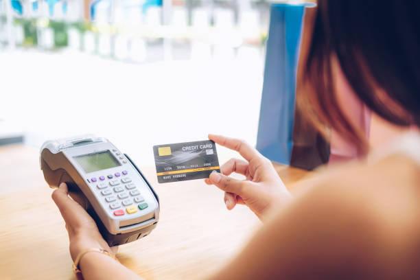 Frau mit Kreditkarte Wischmaschine mit Einkaufstaschen auf dem Tisch. Zahlung mit nfc-Technologie – Foto