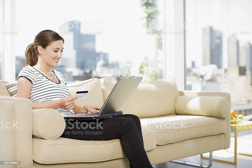Woman using credit card to purchase merchandise on internet stock photo