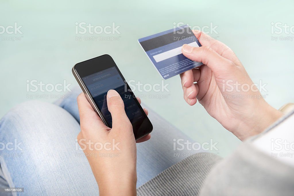 Woman using credit card to shop on smart phone Woman verifies account balance on smartphone with mobile banking application. Banking Stock Photo