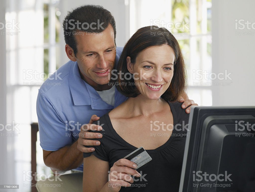 Woman using credit card to shop online with man standing behind her royalty-free stock photo