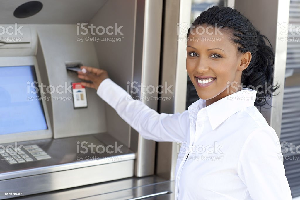 Woman using credit card to withdraw cash money stock photo