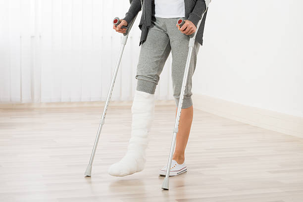 woman using crutches while walking - broken leg stock photos and pictures