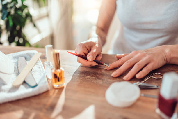 woman using cuticle pusher - cuticle stock pictures, royalty-free photos & images