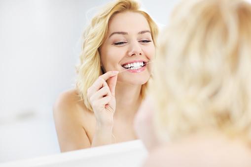 Woman using dental floss stock photo
