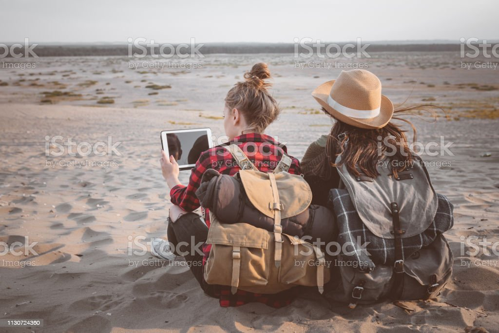 Woman using digital tablet by friend on sand Young female using digital tablet by friend in desert. Explorers are sitting on sand. Women are spending summer vacation together. 20-24 Years Stock Photo