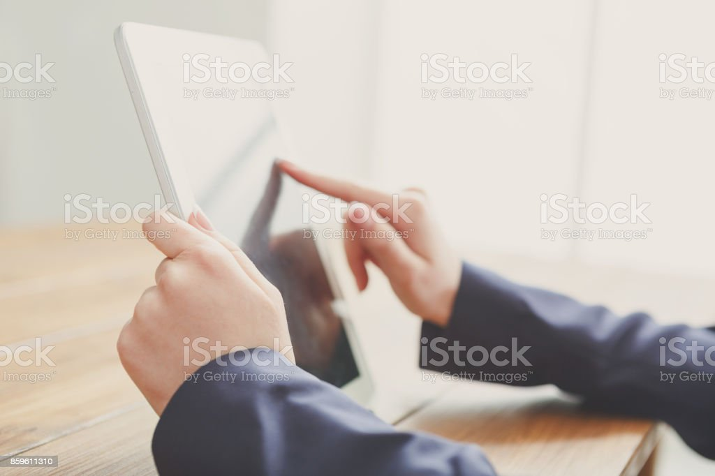 Woman using digital tablet, close up, side view, stock photo