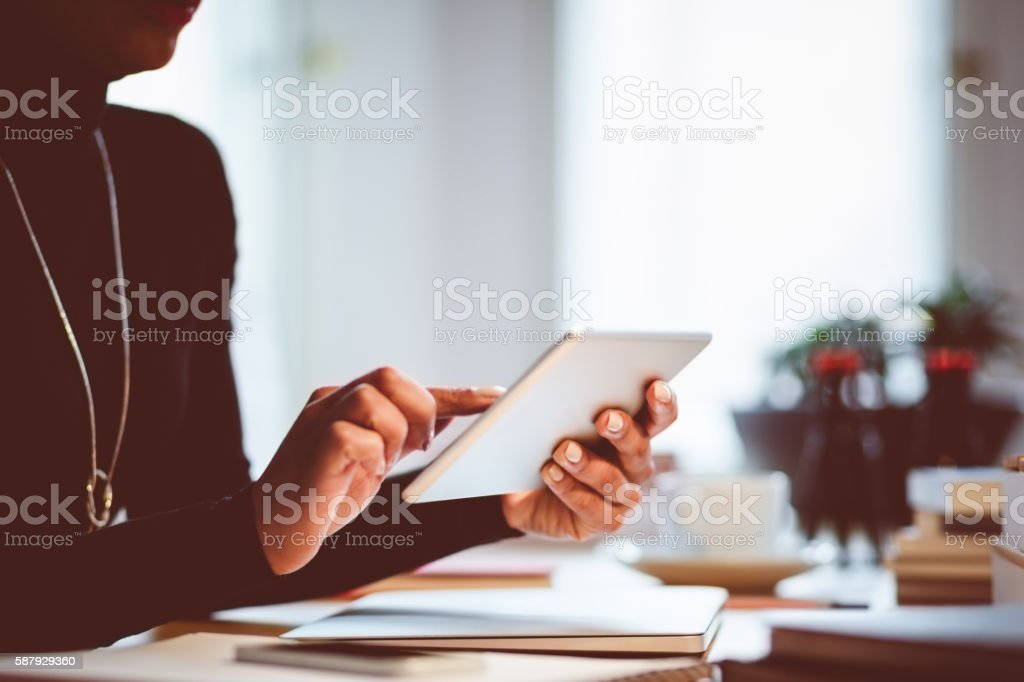 Woman using digital tablet indoors, close up of hands Woman sitting at the desk and using a digital tablet in an office or at home, close up of hands, unrecognizable person. Adult Stock Photo