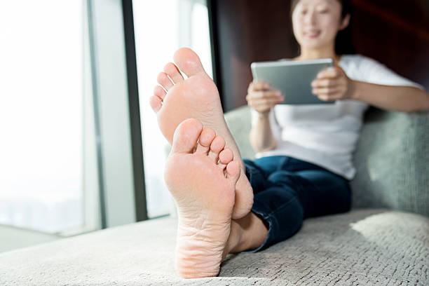 Woman using digital tablet on sofa stock photo