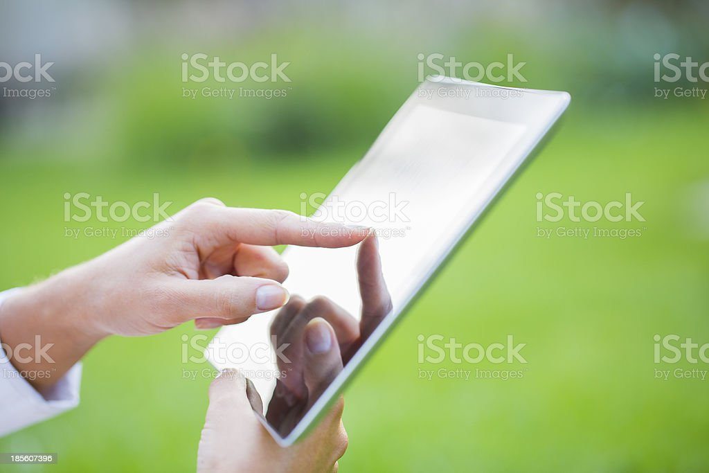 Woman using digital tablet pc in the park. royalty-free stock photo