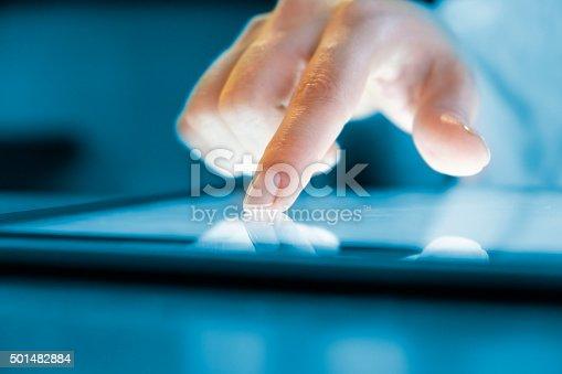 Woman hand touching screen digital tablet pc. Closeup shot. Small depth of field. Soft focus.