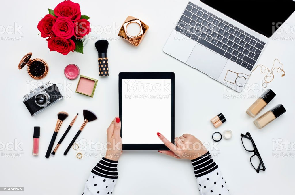 Woman using digital tablet surrounded with beauty products and technologies stock photo