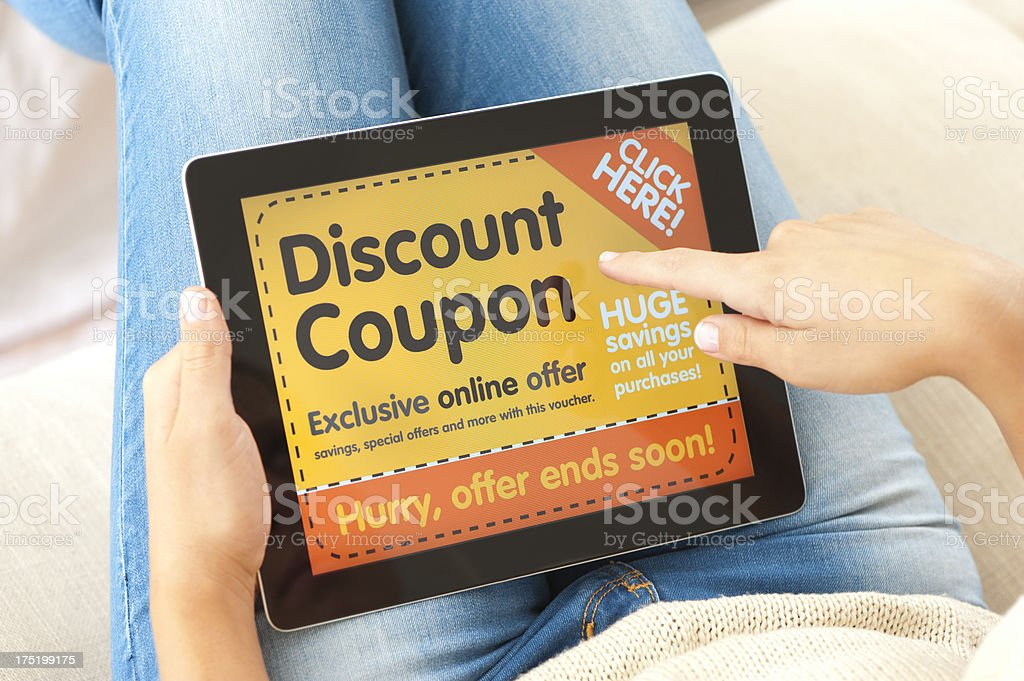 Woman using discount coupon on a digital tablet stock photo