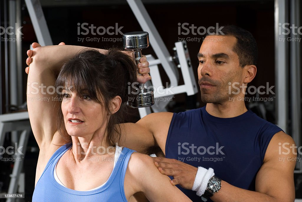 Woman Using Dumbbells With Help of Personal Trainer royalty-free stock photo