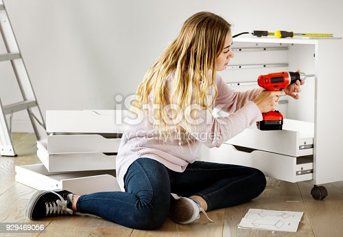 istock Woman using electronic drill install cabinet 929469056