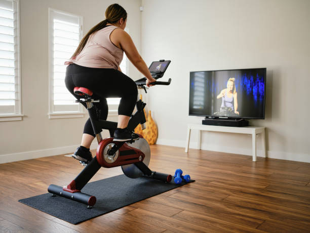 Woman Using Exercise Bike in a Home stock photo