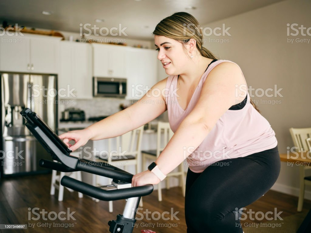 Woman Using Exercise Bike in a Home A woman exercising in her home on an exercise bike. 20-29 Years Stock Photo