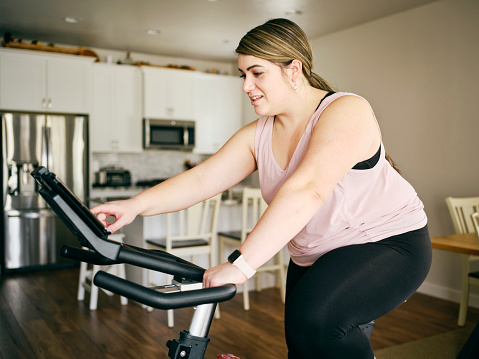 Woman Using Exercise Bike In A Home Stock Photo - Download Image Now
