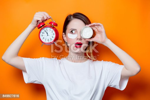 istock Woman using eye patch for her eyes and care lips on orange background 849927616