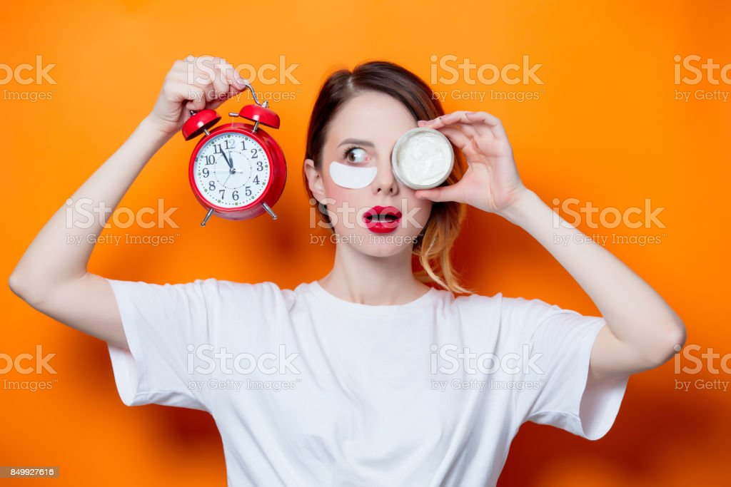 Woman using eye patch for her eyes and care lips on orange background stock photo