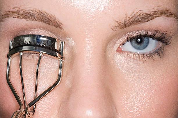 woman using eyelash curlers - 속눈썹 컬러 뉴스 사진 이미지