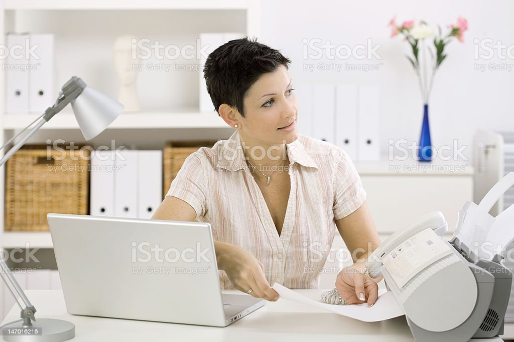 Woman using fax machine stock photo