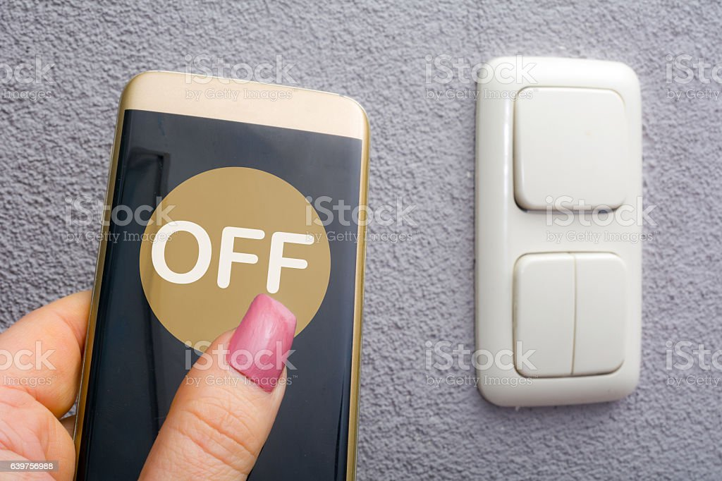 Woman using finger on smartphone to switch off light stock photo