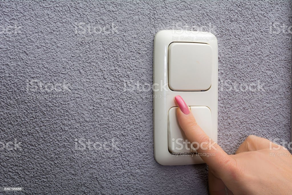 Woman using finger to switch on light stock photo