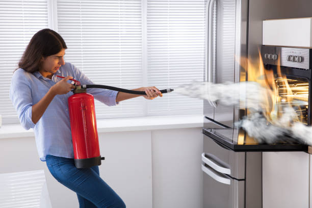 woman using fire extinguisher to put out fire from oven - burned oven imagens e fotografias de stock