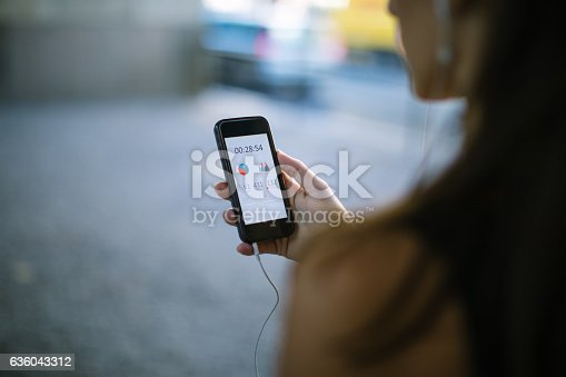 istock Woman using fitness app on smart phone 636043312