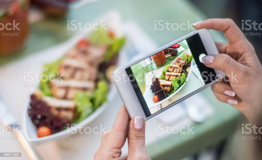 Woman using food app on her cell phone stock photo