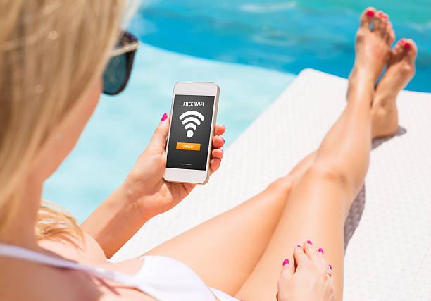 frau mit kostenlosem w-lan zugang auf dem smartphone - iphone gratis stock-fotos und bilder