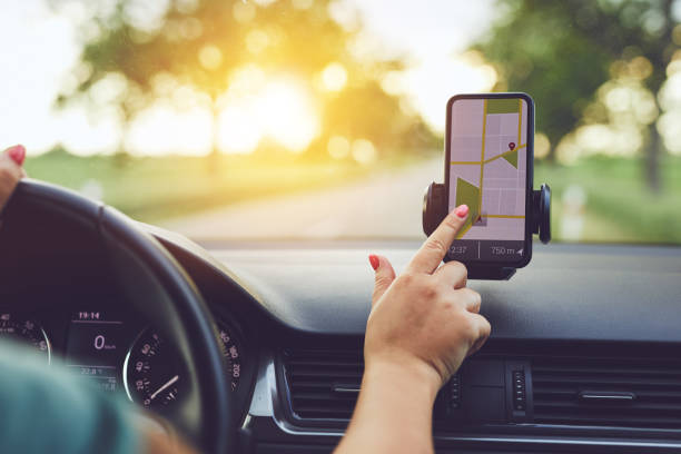 Woman using GPS navigation in mobile phone while driving car at sunset stock photo