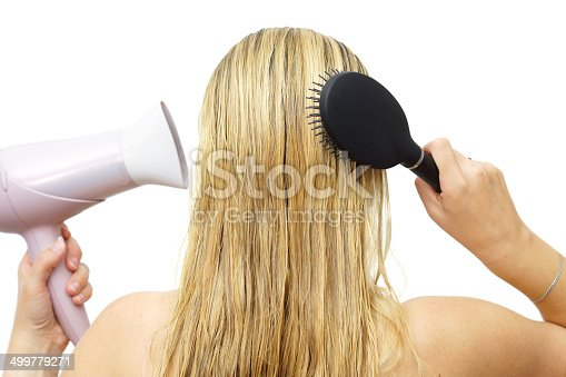 639833996istockphoto Woman using hairdryer  and  comb 499779271