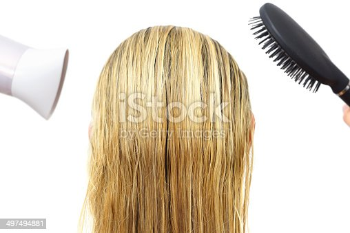 639833996istockphoto Woman using hairdryer  and hair comb 497494881