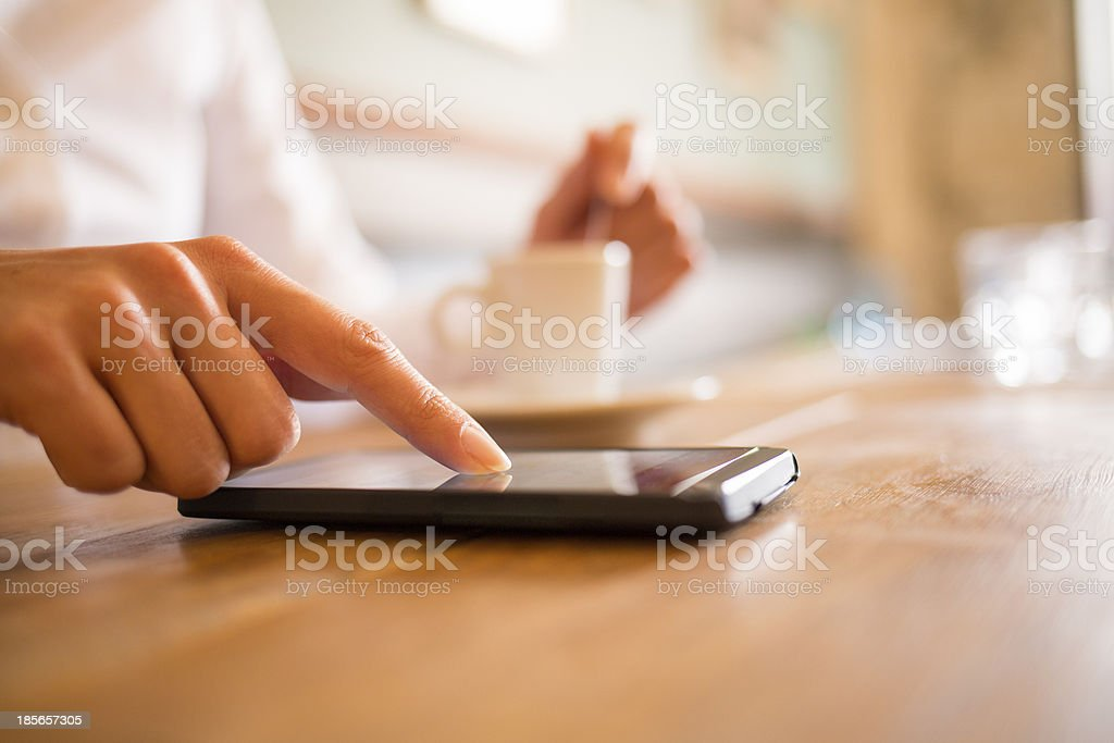 Woman using her cell phone in restaurant, bar stock photo