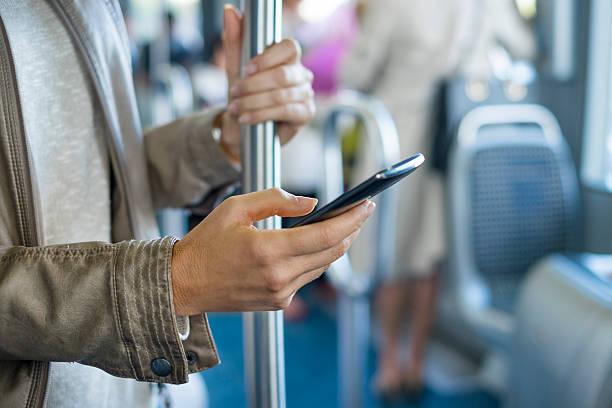 frau mit ihrem handy auf dem bus. straßenbahn. sms, sms - bahn bus stock-fotos und bilder
