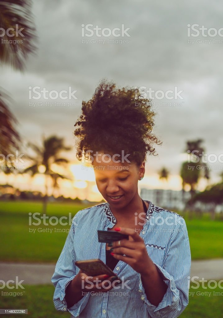 Happy joyful African American woman outdoors in a nature background...