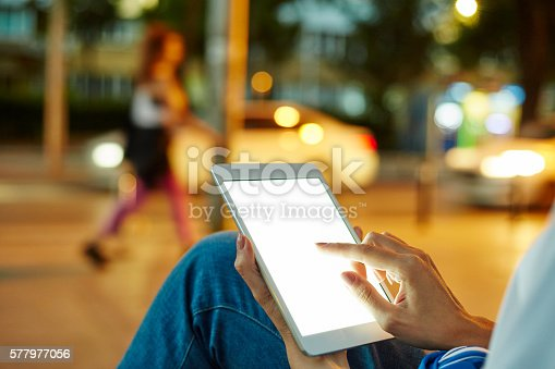 istock Woman Using her Digital Tablet Night Light Background 577977056