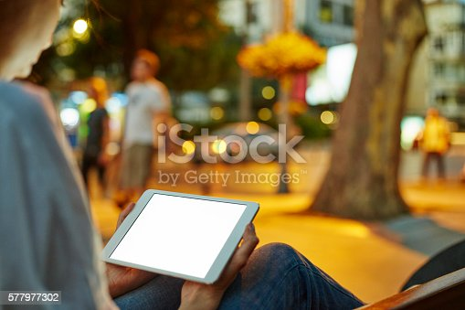 istock Woman Using her Digital Tablet Night Light Background 577977302