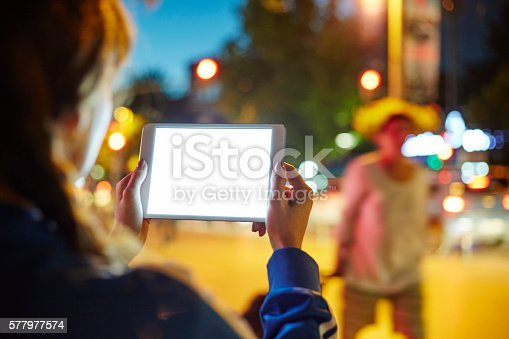istock Woman Using her Digital Tablet Night Light Background 577977574