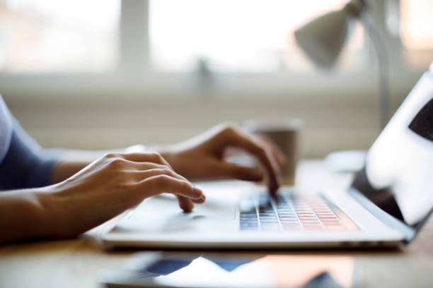 Woman using her laptop for working from home stock photo