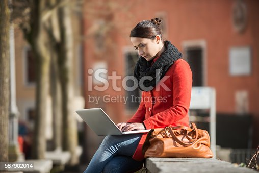 istock Woman using her laptop in the street 587902014