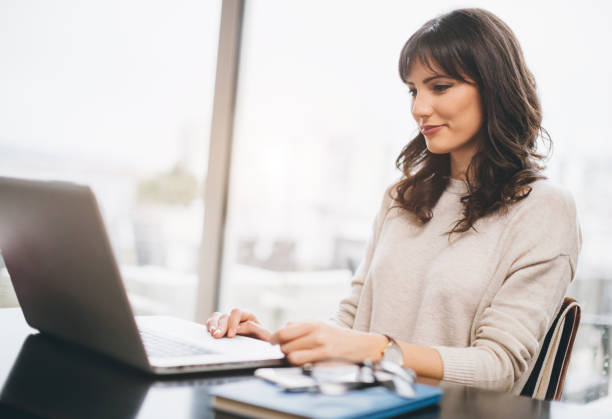 Woman using her laptop stock photo
