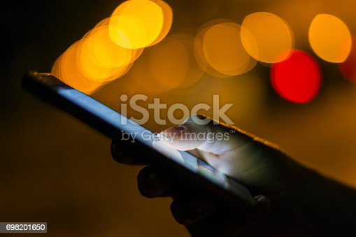 621574390 istock photo Woman using her mobile phone at night 698201650